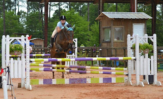 My horse Scooby jumping a jump at a show