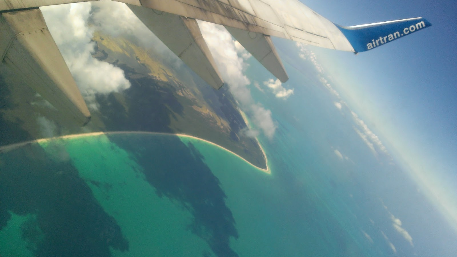 view of a shoreline from an airplane window with wing