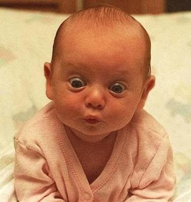 Pequeno bebê olha com olhos muito arregalados para algo.