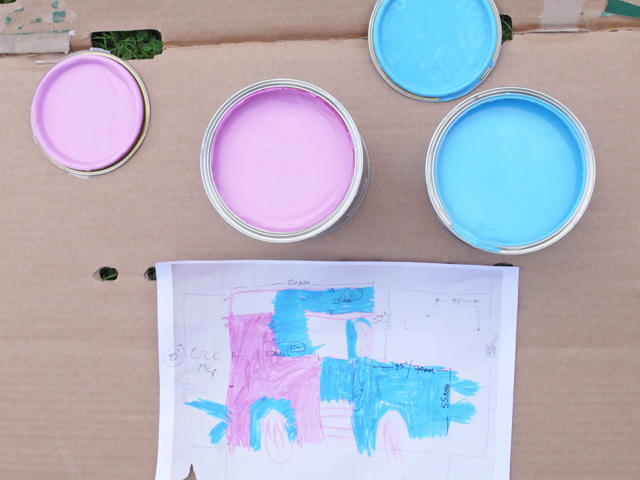 A tin of Blue and pink paint sat onto of some cardboard with a drawing of a zombie tractor.