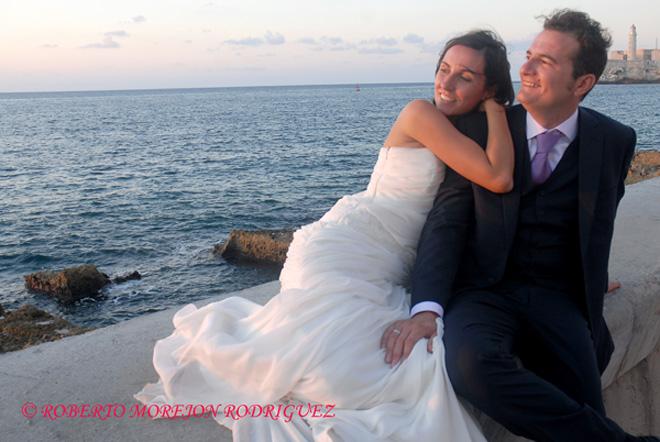 Pedro y Noelia, con sus trajes de boda en el  Malecón, en La Habana, Cuba