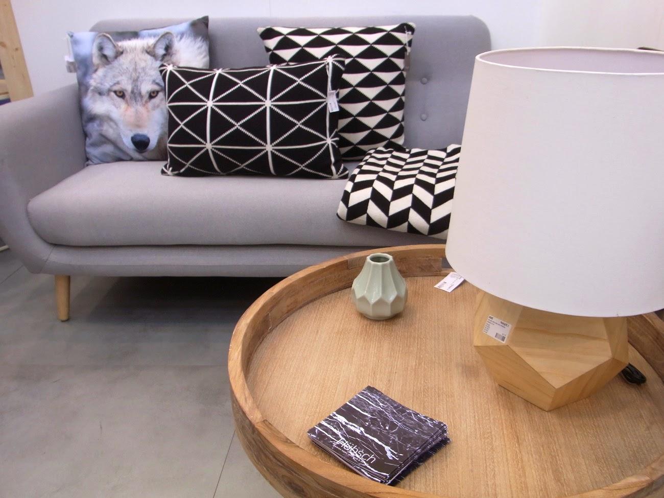 graues Sofa, schwarz weißes Kissen geometrisches Muster, Beistelltisch rund Holz, Tischlampe Lampe mit Holzfuß und hellem Lampenschirm