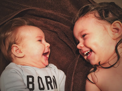 baby brother and sister laughing together
