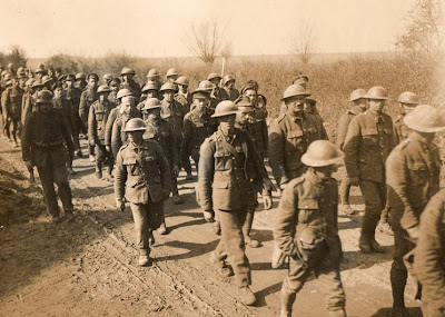 A sepia photograph of dozens of British soldiers, identifyable by their tin hats, trudging unarmed down a dusty road, guarded by German soldiers
