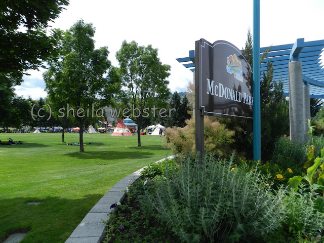 The sign of McDonald Park with the tents and booths set up across the park.