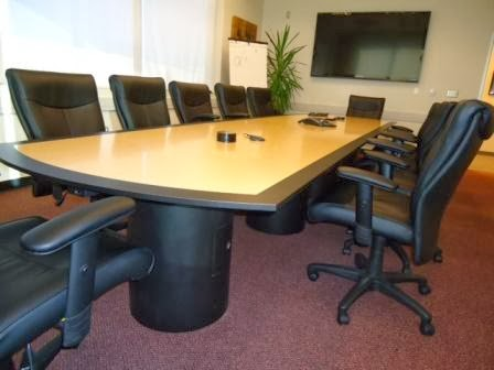 Modern convex shape, fusion maple finish boardroom table seats 14 in Trivascular's Santa Rosa conference room.