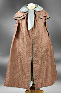 Cloak with capelets, arm slits and piped-bound edgings-front view