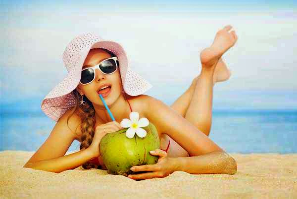 eating coconut water on beach