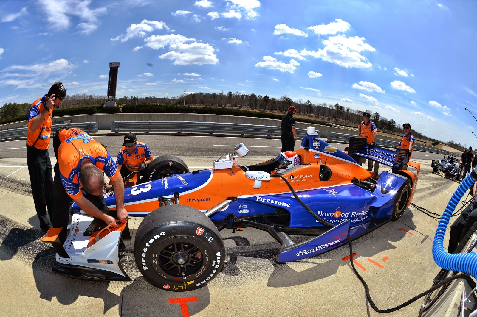 Kimball in pits, with the pit crew working on the front wing.