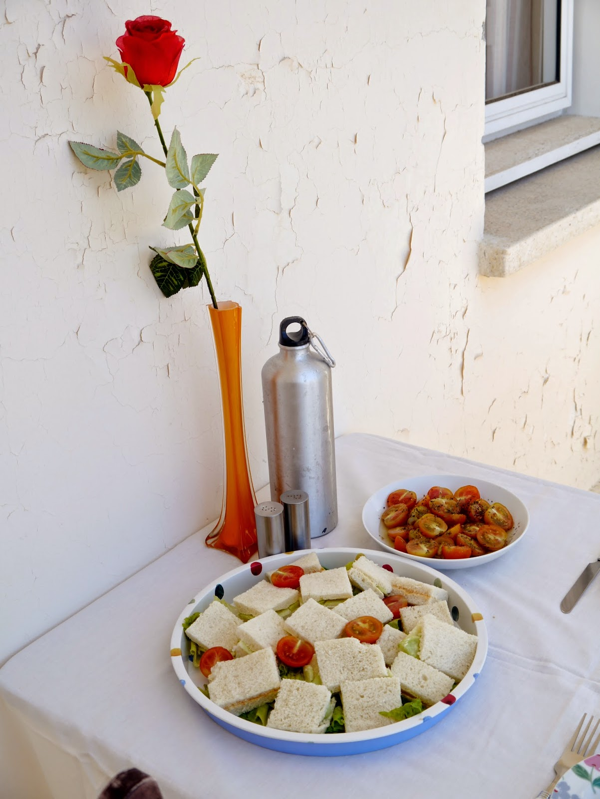 sandwiches, tomatoes and fake rose in vase