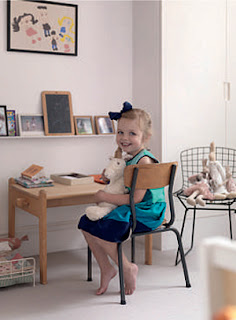 Irenie Cossey's youngest daughter in her room, with a vintage chair and school desk and a Harry Bertoia wire chair, photographed by Tim Young