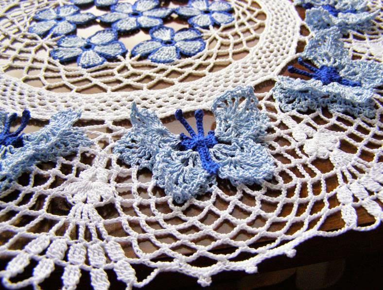 связанная крючком салфетка с цветами и бабочками