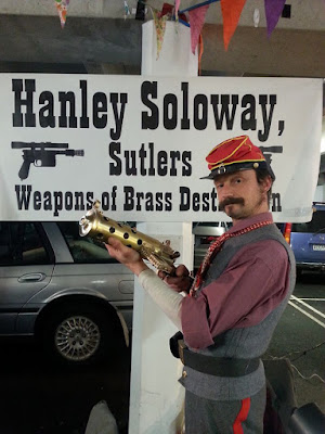 A man dressed in colonial attire, holding a steam-punk-style model gun, in front of a sign saying 'Hanley Soloway, Sutlers: Weapons of brass destruction'
