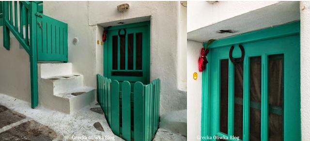 turkusowe drzwi i płotek, podkowa na drzwiach, cebula w rogu drzwi