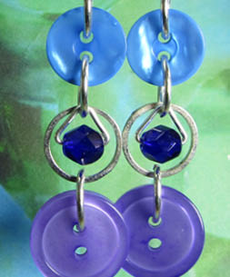 Long strand earrings have small beads encircled in silver rings as a focal point between pretty buttons