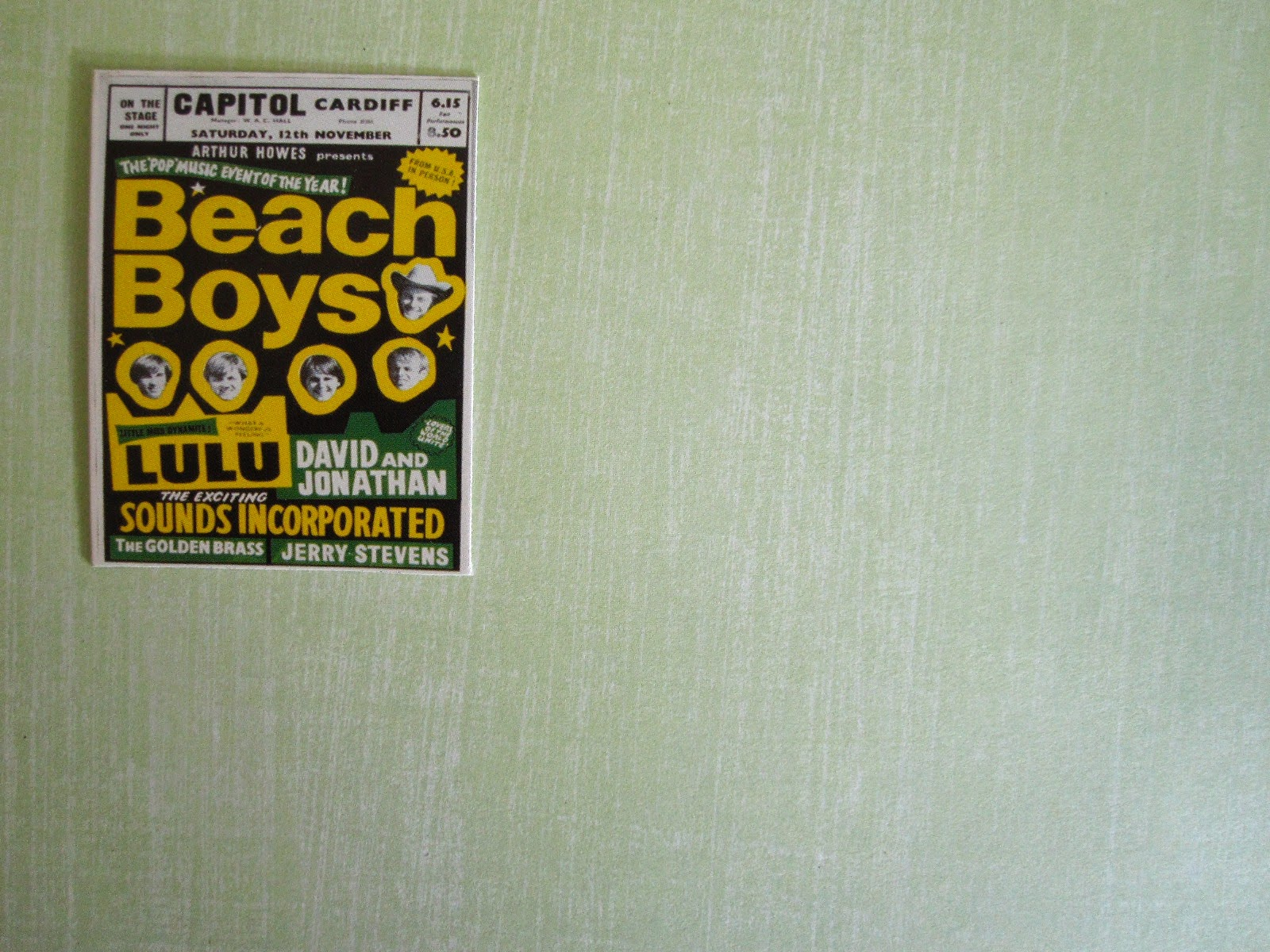 Bright 1960s Beach Boys poster  on a green wall.