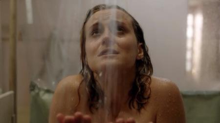 Piper Chapman olhando para o alto com cara de sofrimento pelada tomando banho na prisão, a imagem só mostra do ombro nu pra cima.