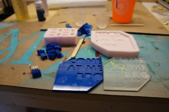 blue resin cast parts with molds in background