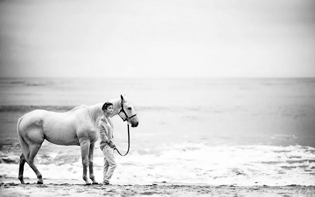 Zwart wit foto van een vrouw met paard op het strand