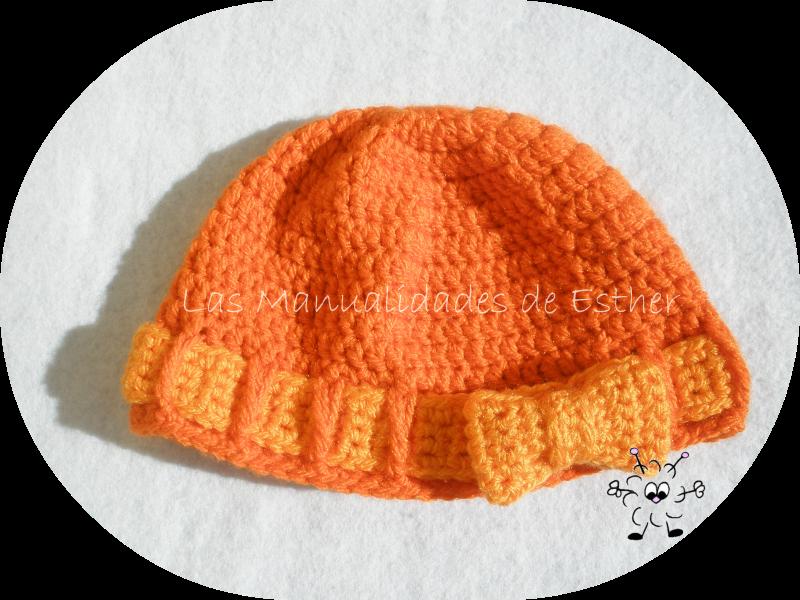 gorro de lana naranja realizado a crochet con cinta y lazo también a crochet