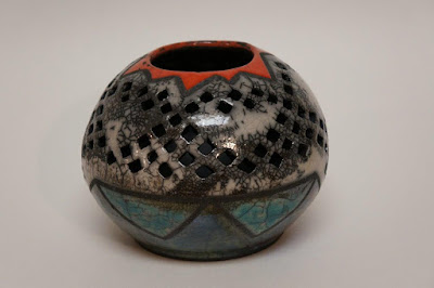 Beautiful pierced ceramic pottery vessel with bright raku glazes.