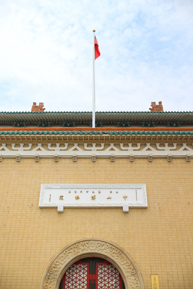 the ROC flag flies above an intricate red paneled doorway at the National Palace Museum in Taiwan