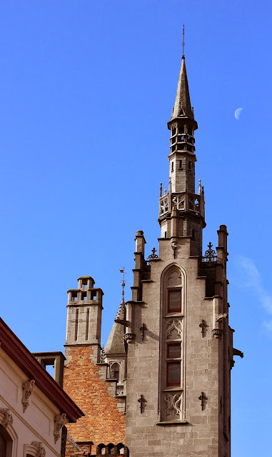 Tower on the edge of the Burg in Bruge against a blue sky with the moon in the background