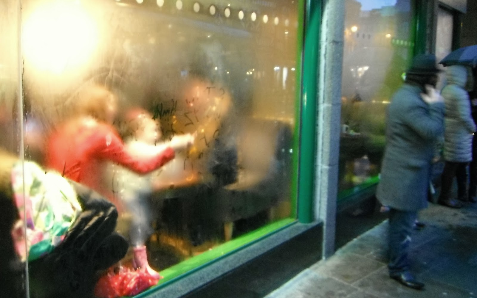 A mother and child draw shapes in the condensation on a window.