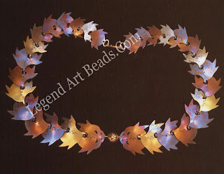 A CAD program was used to laser-cut the pieces of steel and anodized titanium in this metal necklace. The individual pieces were shaped, anodized, and chemically colored before being linked on a silk thread.