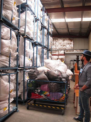 Man looking at a pallet rack holding large bags full of clothing.