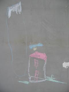 Szöveg: Ha nem vagy elég szemfüles, akkor bizony új díszítőelemmel fog bővülni a házatok, szobátok fala...  Kép: szürkére vakolt házfalon színes, krétával firkált gyerekrajz. Egy óriási téglalap alakú valami, aminek a teteje sárgára van festve. Ha jól megnézed, akkor hegyre hajaz. E mellett egy piros tetejű, egy ablakos, egy ajtós (mindkettő piros és középen van) házikó, ami felett egy felhő mögül alól kikandikáló nap néz ki.