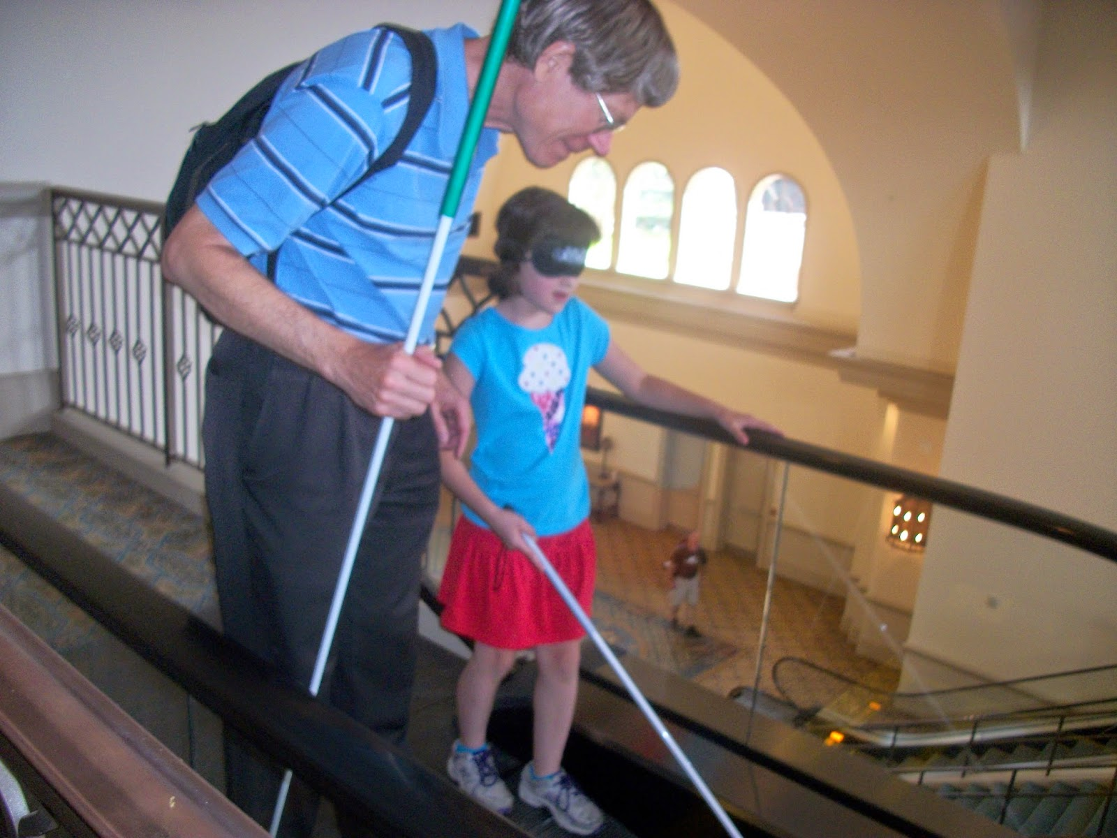 a blind girl with a white cane and instructor at an escalator