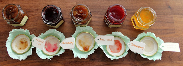 five mini jams opened with lids upturned traditional packaging with cloth over lid