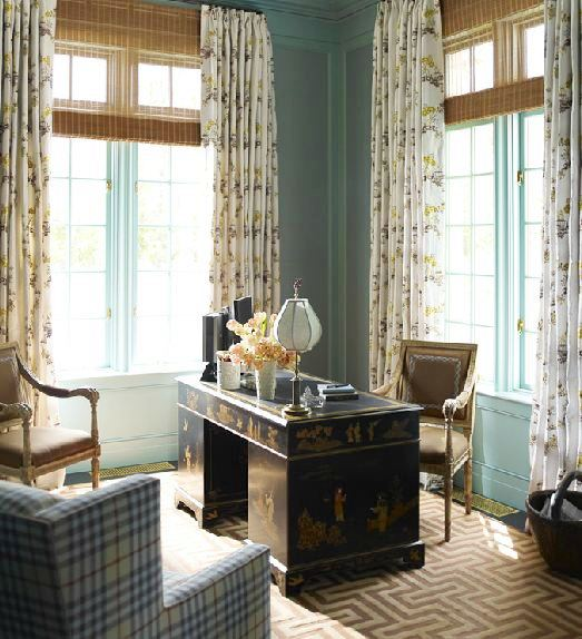 Library in Katie Ridder's home with a bold brown and cream graphic rug, rattan blinds, a plaid armchair across a Chinoisserie desk, blue walls with encasement windows covered in floor length floral curtains