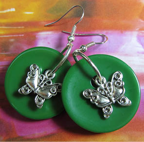 Drop dangle earrings have silver butterfly charms layered over big green buttons