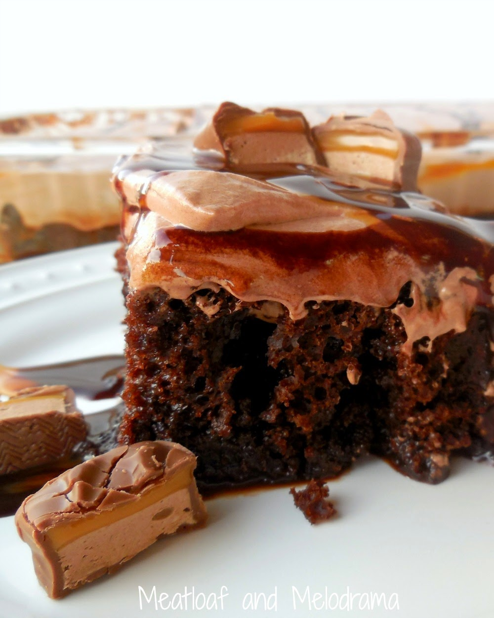 chocolate poke cake with chocolate and caramel syrup and milky way bars.