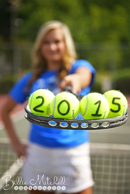 senior girl hold tennis racket with tennis balls on it with 2015 written on the balls