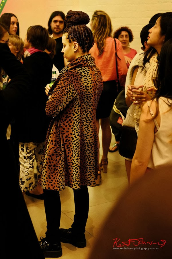 Leopard print coat, braided hair black tights and heavy thick soled black shoes; Serve the People art opening at White Rabbit Gallery.