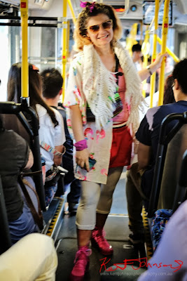 Flora in Pink singlet and Red shorts, white jacket scarf and leggings with pink runners - photographed on the 426 bus on City Road by Kent Johnson.
