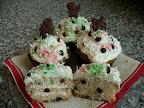 Karácsonyi csokicseppes kókuszos muffin, aminek a tetején kókusztejes krém és kókuszreszelék van, mikulásos, hóemberes és angyalkás csokival díszítve.