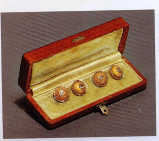 Below, a pair of yellow gold cufflinks of bombe form, enameled in opalescent tones of apricot to pink on sunray back-grounds, with rose diamond borders and brilliant diamond centers