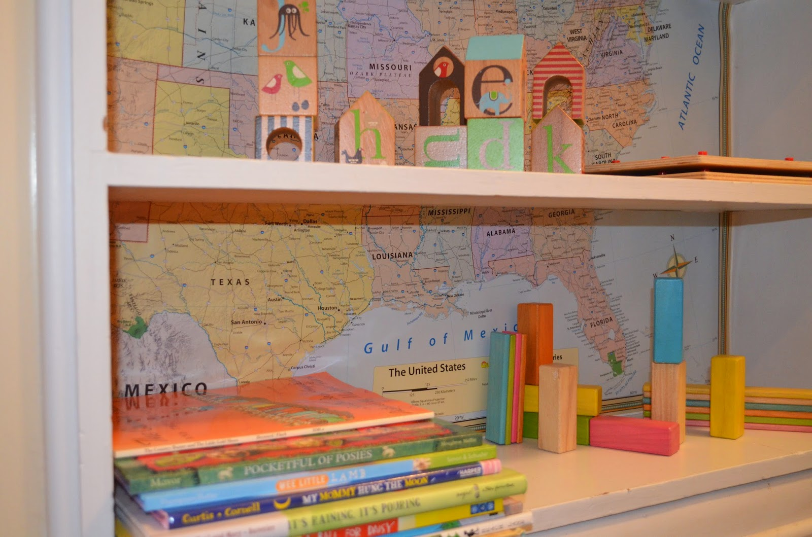 my high shelf with my special vintage books i just cut up a us map for a little background paper on the shelving