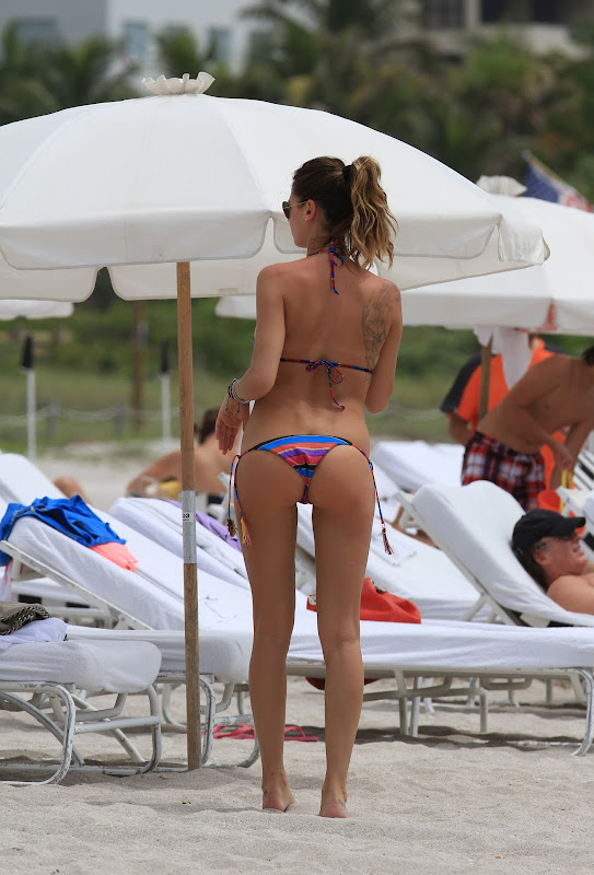 MELISSA SATTA beside white beach umbrella