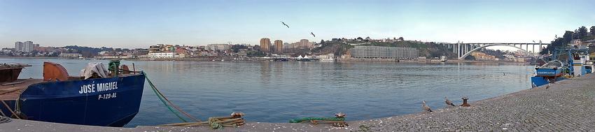 Foto panorama a cerca de 180 graus. À esquerda um barco ancorado, ao fundo a margem oposta, no Porto e à direita a Ponte da Arrábida