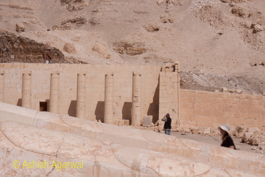 Person viewing the ruins of the pillars without a roof at the Hatshepsut mortuary temple in Egypt