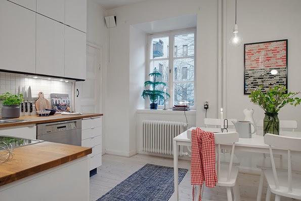 Cocina de piso pequeño con muebles blancos y roble