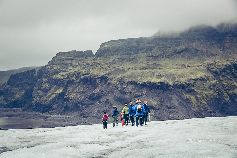Gruppe mit Schutzhelm und Eispickel auf dem Gletscher