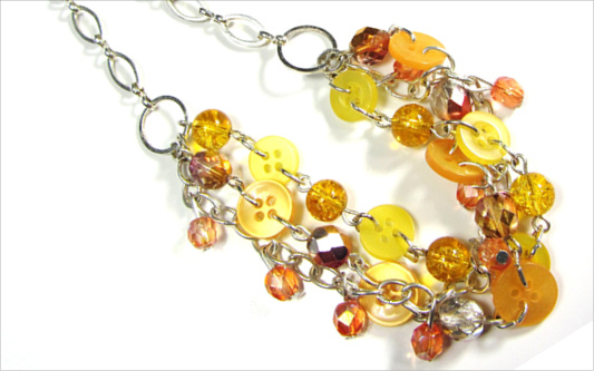 3 strand necklace has shiny yellow and gold beads with buttons