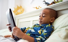 Young boy in bed reading on an electronic device