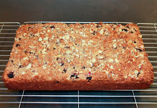 Blackberry crumble cake cooling on a wire rack before cutting